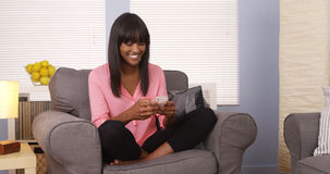 African woman using smartphone on couch Royalty Free Stock Photo