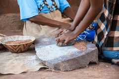 African woman grinding. African woman in the village grinding traditionally some seeds Stock Photography