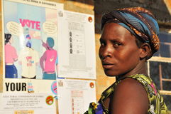 African woman waiting to vote. Woman waiting  to vote at polling station in front of voter education poster, Zambia tripartite elections 2011 Stock Image