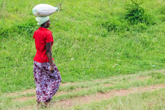 African woman. Tanzania, Arusha town. A young woman walks carrying a heavy bag on his head because of the long distances Royalty Free Stock Photography