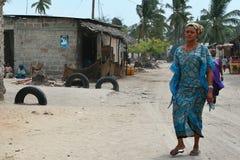 African woman walking on dirt road of coastal fishing village. Stock Photos