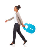 African woman walking lock. Side view of african american woman walking with lock symbol on white background royalty free stock images
