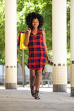 African woman walking with shopping bags and mobile phone Royalty Free Stock Photography