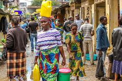 African woman walking with a yellow tank on the head Royalty Free Stock Photos