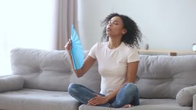 African woman waving fan feeling hot suffering from heat indoors. African american young woman feeling hot suffering from high temperature summer heat problem stock video