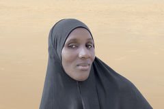 African woman wearing a black cotton veil in the desert Stock Photos