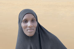 African woman wearing a black cotton veil in the desert Royalty Free Stock Image