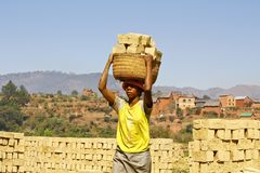 Africans woman working hard in brickyard. African woman working hard in brickyard - Madagascar royalty free stock image