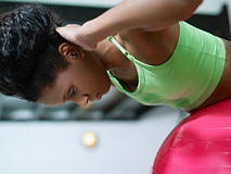 African woman working out on fitball in gym Stock Image