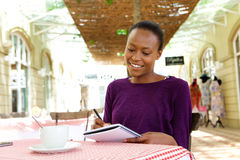 African woman writing in a cafe Stock Photos