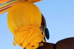 African woman with yellow head scarf. From the back view Royalty Free Stock Images