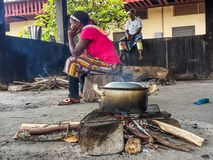 African women cooking meal over simple wood fire at Albert Schwe Royalty Free Stock Image