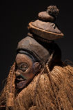 African wooden masks. With hair. On black background stock photography
