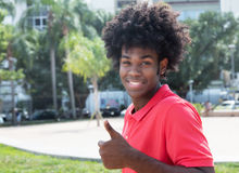 African young adult with typical afro hairstyle showing thumb Stock Photos