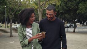 African young couple using mobile while walking on street stock footage