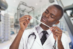 African young doctor. Observing a tape measure stock image