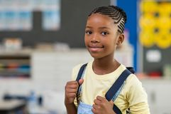 Girl wearing backpack at school. African young girl with blue backpack looking at camera. Pretty and satisfied black schoolgirl with rucksack smiling in class royalty free stock photo