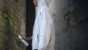 African young male painting graffiti by spray on abandoned building wall, street. Stock footage stock video