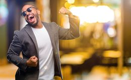 African young man. African american man with beard happy and excited celebrating victory expressing big success, power, energy and positive emotions. Celebrates Royalty Free Stock Image