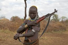 African young man with assault rifle. African young man of the Mursi ethnic group is carrying an assault rifle at the village at the Mago National Park, Ethiopia Stock Photos