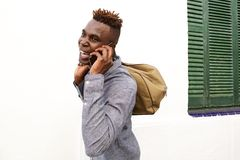 African young man laughing outdoors with bag and mobile phone. Portrait of african young man laughing outdoors with bag and mobile phone Royalty Free Stock Photography