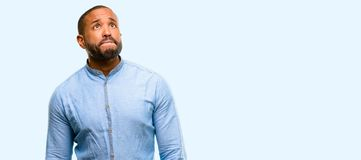 African young man over white background. African american man with beard doubt expression, confuse and wonder concept, uncertain future over blue background stock photos