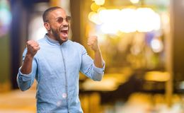 African young man over white background. African american man with beard happy and excited expressing winning gesture. Successful and celebrating victory Stock Photography