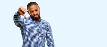 African young man  over white background. African american man with beard showing thumbs down unhappy sign of dislike, negative expression and disapproval  over Stock Photography