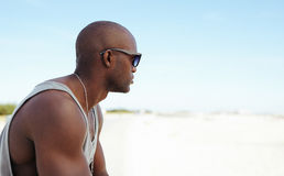 African young man sitting at the beach Royalty Free Stock Image