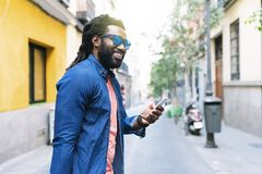 African Young Man using mobile. African Young Man Using Mobile In The Street Stock Images