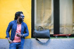 African Young Man Using Mobile In The Street. Outdoor Portrait Of Handsome African Young Man Using Mobile In The Street Stock Images