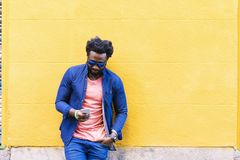 African Young Man Using Mobile In The Street. Outdoor Portrait Of Handsome African Young Man Using Mobile In The Street Stock Image