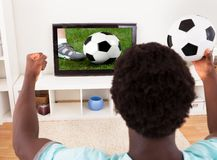 African Young Man Watching Television Holding Football Stock Image