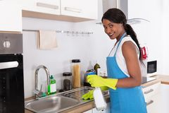 Woman Cleaning Kitchen Sink With Spray Bottle. African Young Woman Cleaning Kitchen Sink With Spray Bottle In Kitchen royalty free stock photography