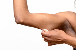 African young woman  pinching her arm. African young woman displaying the loose skin or flab due to ageing on her upper arm pinching it between her fingers Royalty Free Stock Image