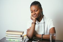 African young woman sitting at table with books at home. African american young woman sitting at table with books at home Royalty Free Stock Photo