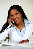 African young woman speaking on phone. Portrait of an african young woman laughing and speaking on phone at home indoor Stock Images