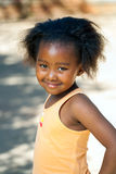 African youngster outdoors. Portrait of cute African youngster in orange vest outdoors Stock Photos