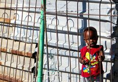 African Youth. A small curious poor african child watches through the metal bar barbed wire fence of his shanty with a western disney shirt in the township of Stock Images