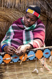 African Zulu woman weaves straw carpet. Royalty Free Stock Photography