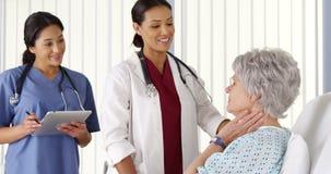 AfricanAmerican doktor som talar till den äldre kvinnapatienten med sjuksköterskan Arkivbild