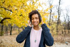 Africanamerican girl listening to music in the autumn park.  royalty free stock photos