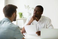 Africano atento sério hora que escuta o candidato no trabalho inter imagem de stock royalty free