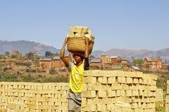 Africans woman working hard in brickyard. African woman working hard in brickyard - Madagascar royalty free stock photo