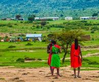 Afrika, Kenia, Masai Mara, Krieger plaudert nahe ihrem Dorf auf Savanne lizenzfreies stockbild