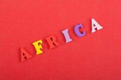 AFRIKA ord på röd bakgrund som komponeras från träbokstäver för färgrikt abc-alfabetkvarter, kopieringsutrymme för annonstext lär Royaltyfria Bilder