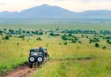 Afrika safarijeep som kör på nationalpark för Masai Mara och Serengeti royaltyfria foton