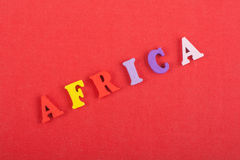 AFRIKA-Wort auf dem roten Hintergrund verfasst von den hölzernen Buchstaben des bunten ABC-Alphabetblockes, Kopienraum für Anzeig Lizenzfreie Stockbilder