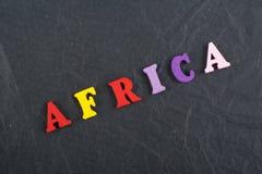 AFRIKA-Wort auf dem schwarzen Bretthintergrund verfasst von den hölzernen Buchstaben des bunten ABC-Alphabetblockes, Kopienraum f Lizenzfreie Stockfotos