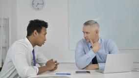 Afrikaan en Grey Hair Businessman Discussing Project op Laptop stock videobeelden